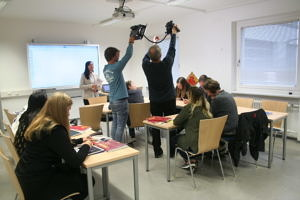 """Die Teilnehmer an der Aktion """"Filmdreh für das E-learning Projekt"""" simulieren einen typischen Unterrichtsverlauf mit Tablets, das ganze wird gefilmt. Die Teilnehmer sitzen an Tischen und nutzen Lehrbuch, sowie die Tabletts und schreiben auf diesen u.a. Schriftzeichen."""