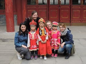 ExkursionsteilnehmerInnen mit einer gruppe chinesischer Kinder in lokaler traditioneller Kleidung.