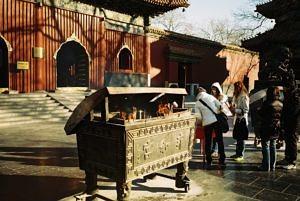 Eine bronzene Truhe mit Räucherstäbchen darin vor einem chinesischen Tempel.