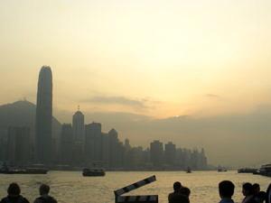Die Skyline von Hongkong vor dem Hintergrund des Victoria Peak bei Abenddämmerung.