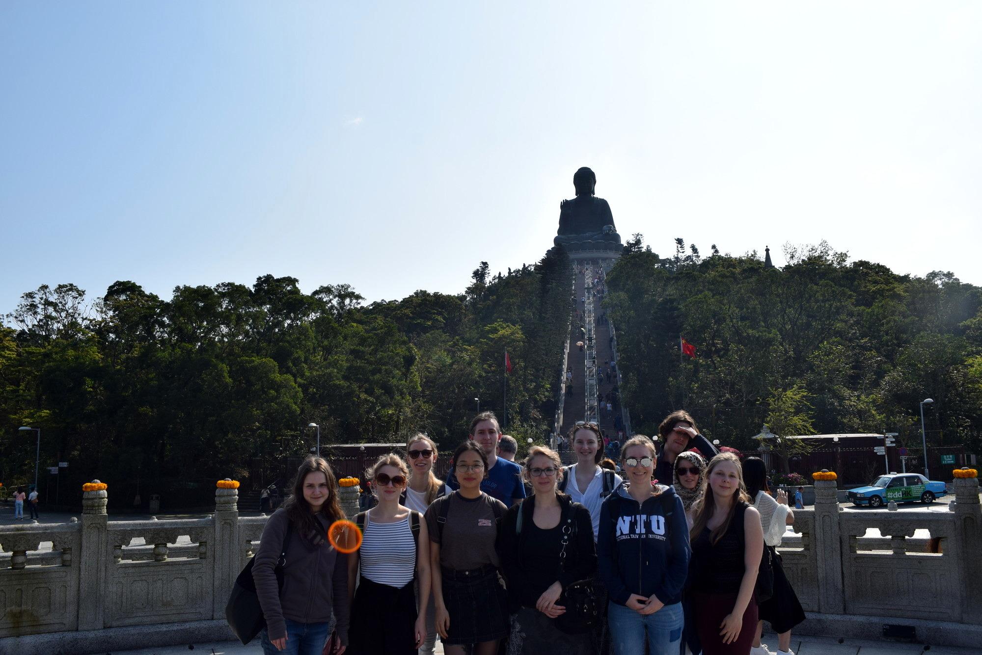 Gruppenfoto der ExkursionsteilnehmerInnen vor dem Tai Tan Buddha in der Nähe von Hongkong während der China-Exkursion 2019.